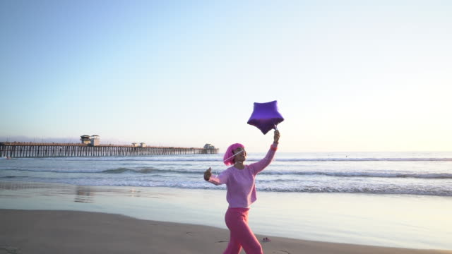 ws young woman with pink hair playing with a balloon on the beach. - pink hair stock videos and b-roll footage
