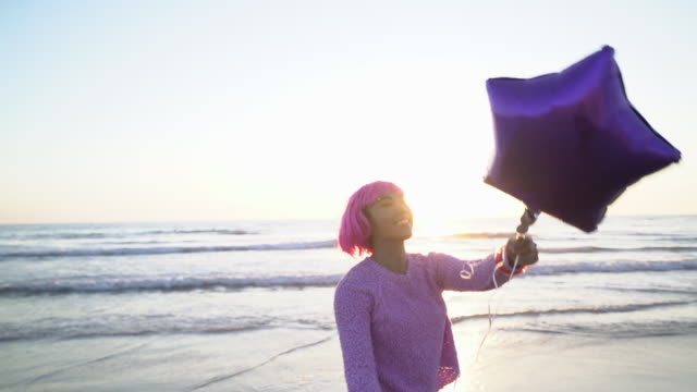 MS SM Young woman with pink hair playing with a balloon on the beach