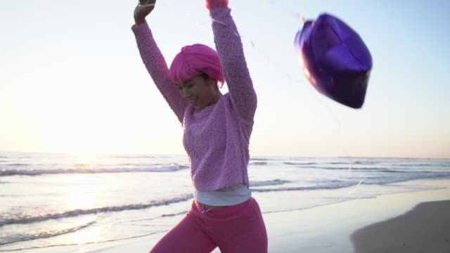 sm young woman with pink hair playing with a balloon on the beach. - pink hair stock videos & royalty-free footage