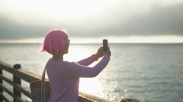 ms young woman with pink hair taking a photo of the ocean. - hot pink stock videos & royalty-free footage