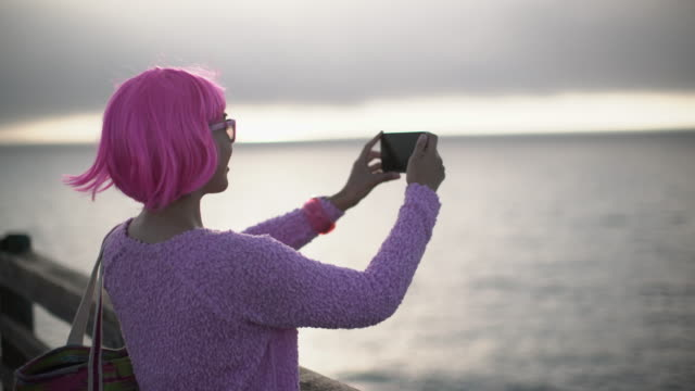 ms young woman with pink hair taking a photo of the sea - pink hair stock videos & royalty-free footage