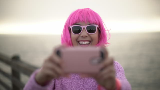 cu young woman with pink hair taking a selfie - bangs stock videos and b-roll footage