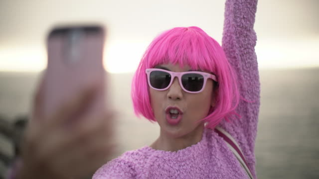 cu young woman with pink hair taking photos - bangs stock videos and b-roll footage