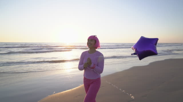 WS Young woman with pink hair walking down the beach with a balloon