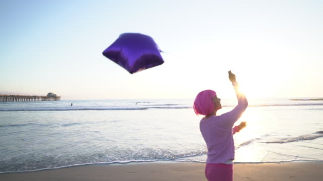 sm ms young woman with pink hair walking down the beach with a balloon - pink hair stock videos & royalty-free footage