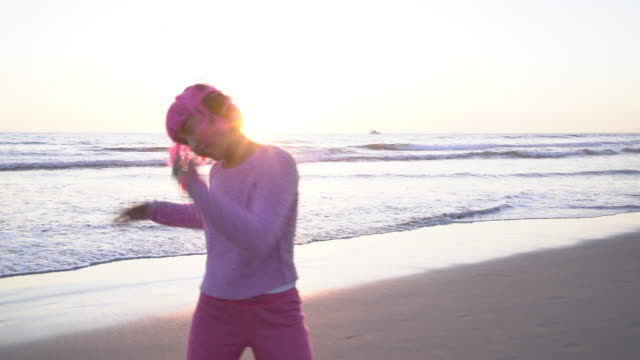 ms young woman with pink hair wearing headphones and dancing on the beach - pink hair stock videos & royalty-free footage