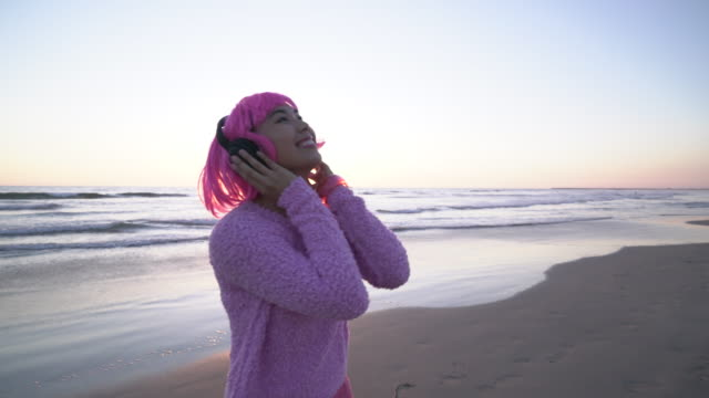 ms young woman with pink hair wearing headphones listening to music - pink hair stock videos & royalty-free footage