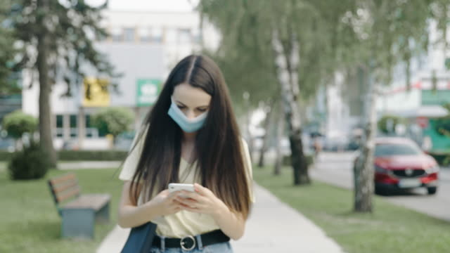 slo mo junge frau mit schützender gesichtsmaske, die ihr smartphone beim gehen im öffentlichen park herausnimmt - young women stock-videos und b-roll-filmmaterial