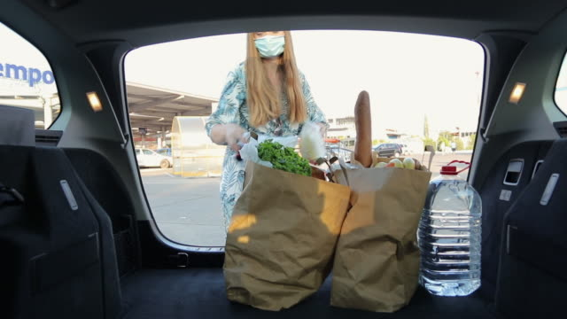 young woman with protective face masks packing car trunk with groceries - paper bag stock videos & royalty-free footage