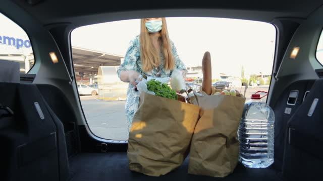 vidéos et rushes de jeune femme avec des masques protecteurs d'emballage de coffre de voiture avec l'épicerie - sachet en papier