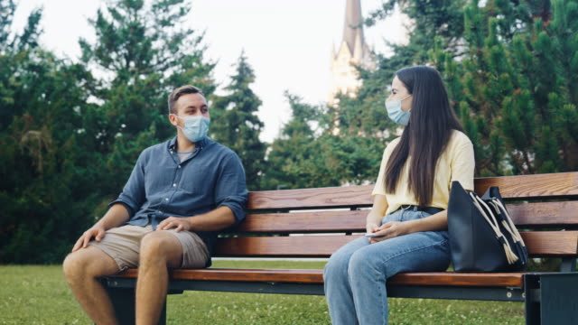 slo mo young woman with protective face masks using phone and meeting friend on the bench in public park - bench stock videos & royalty-free footage