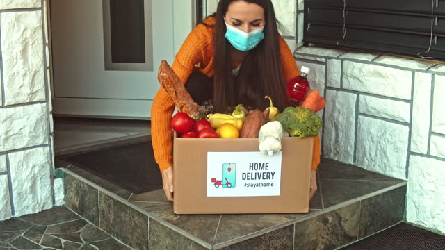 slow motion young woman with protective mask picking up the food box from the doorstep - groceries stock videos & royalty-free footage