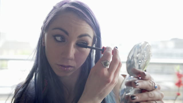 vídeos de stock, filmes e b-roll de a young woman with purple hair doing her hair and make-up - lip ring