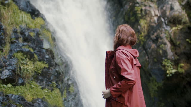young woman with rain jacket looking up at waterfall - waterfall stock videos & royalty-free footage