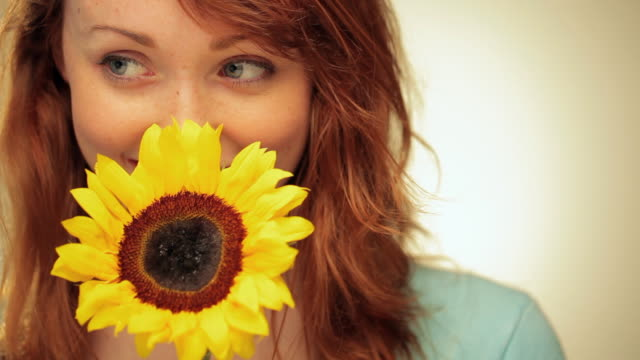 CU Young Woman with Red Hair Holding Sunflower and Smiling