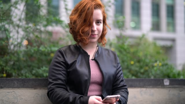 young woman with red hair using mobile - portrait - pardo brazilian stock videos & royalty-free footage