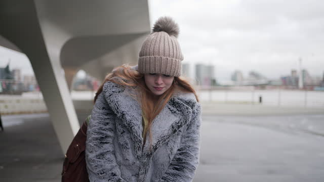 vídeos de stock e filmes b-roll de a young woman with red hair wearing a coat and bobble hat - cabelo natural
