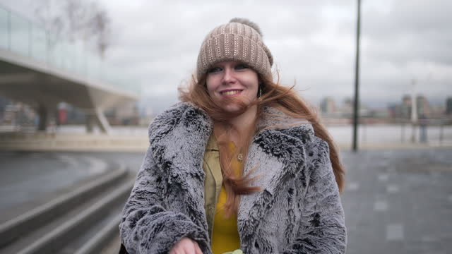 a young woman with red hair wearing a coat and bobble hat - winter coat stock videos & royalty-free footage