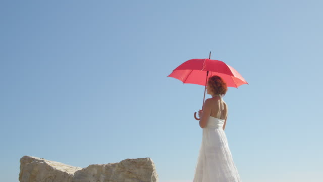 young woman with red umbrella walking against blue sky, sitting down on rock