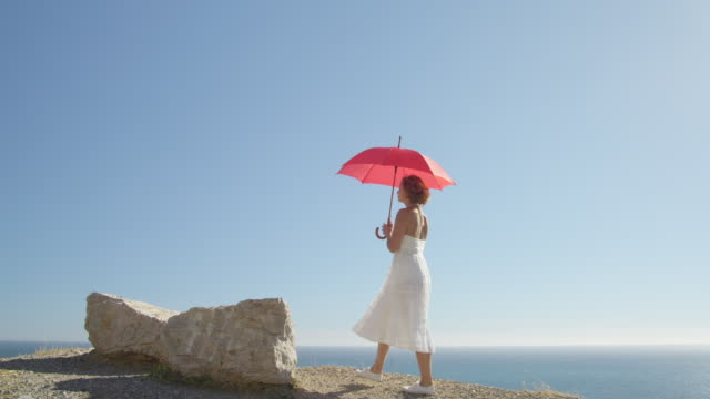 young woman with red umbrella walking against blue sky, sitting down on rock - ドレス点の映像素材/bロール