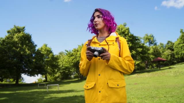 vídeos y material grabado en eventos de stock de jovencita con cámara retro explorando la naturaleza - sólo mujeres jóvenes