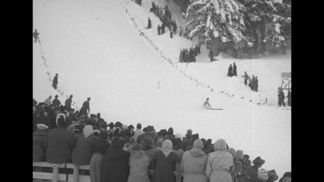 Young woman with ribbon pinned to her jacket smiles / VS view from landing area as jumpers land / large crowd at base of slope / VS skiers land...