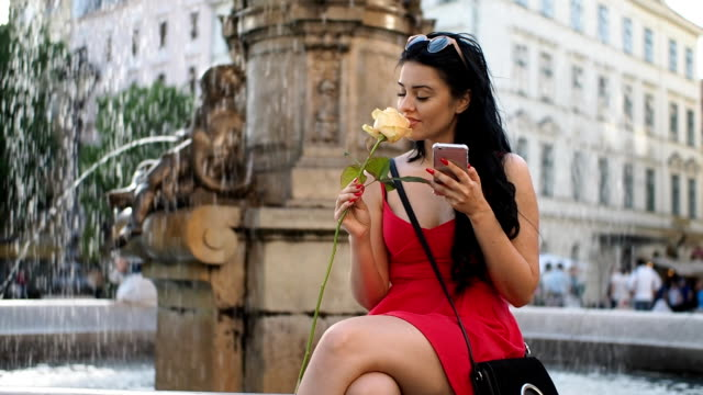Young woman with rose flower and smartphone on the fountain - SLOW MOTION