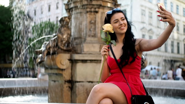 Young woman with rose flower and smartphone on the fountain