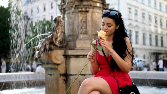 Young woman with rose flower on the fountain - SLOW MOTION
