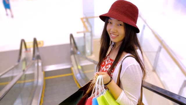 Young woman with shopping bags in mall