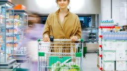 young woman with shopping cart stands in supermarket