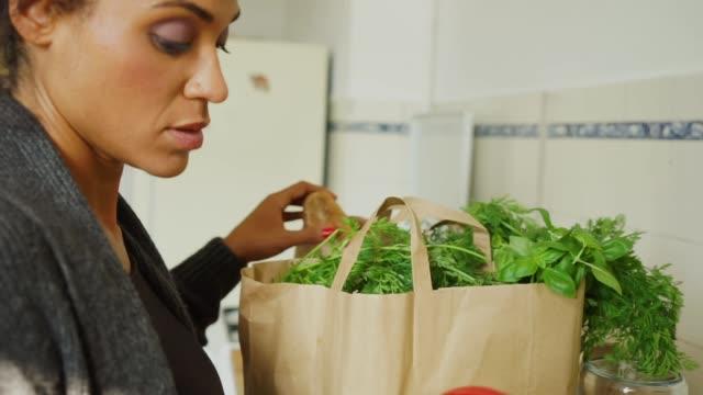 Jeune femme et de ses boutiques dans cuisine