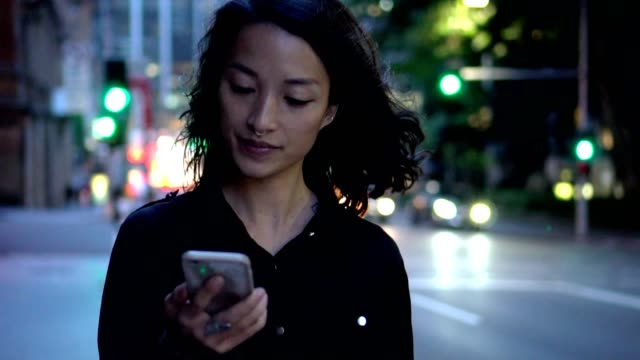 young woman with smart phone  walking on the street at night - guardare in una direzione video stock e b–roll