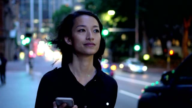 young woman with smart phone  walking on the street at night - white collar worker stock videos and b-roll footage
