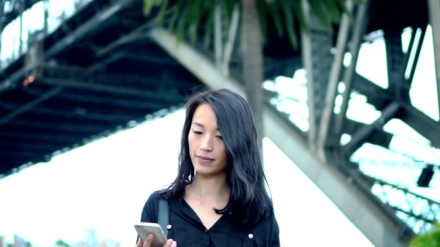 young woman with smart phone  walking on the street - black hair stock videos & royalty-free footage