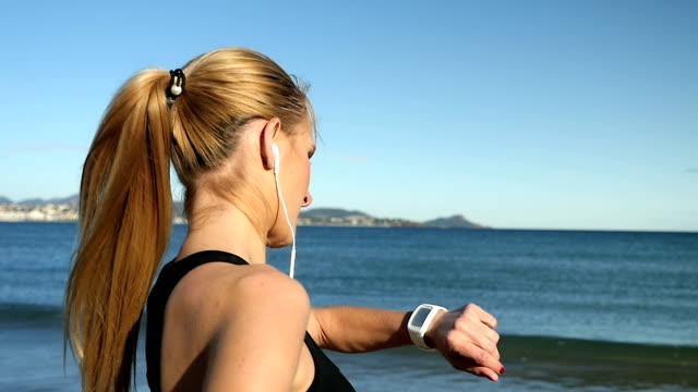 Young woman with smart watch and earbud
