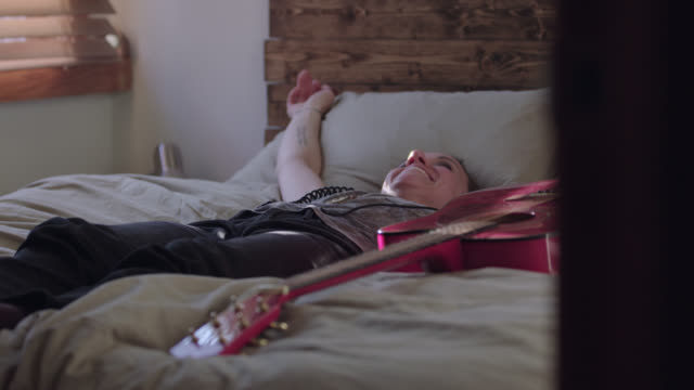 stockvideo's en b-roll-footage met ws slo mo. young woman with smartphone and headphones falls back on bed happy. - hoofdtelefoon