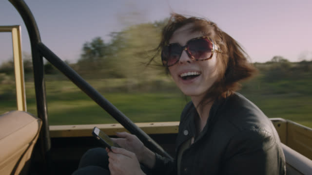 Young woman with smartphone laughs with friends in backseat of classic Ford Bronco