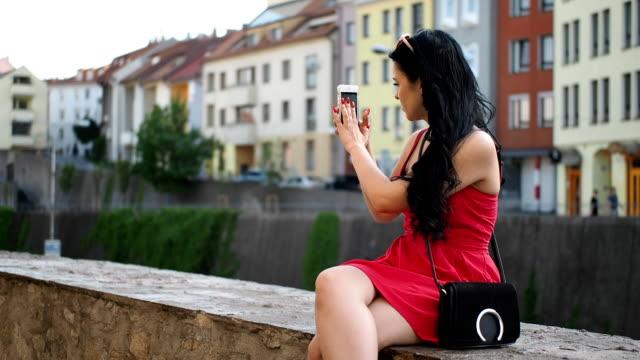 壁の上に座ってのスマート フォンを持つ若い女性 - ufo点の映像素材/bロール