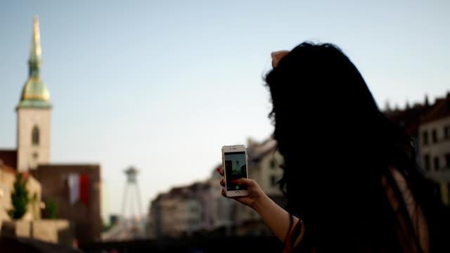 young woman with smartphone sitting on the wall - muro di recinzione video stock e b–roll