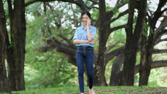 Young woman with smartphone walking in the park.