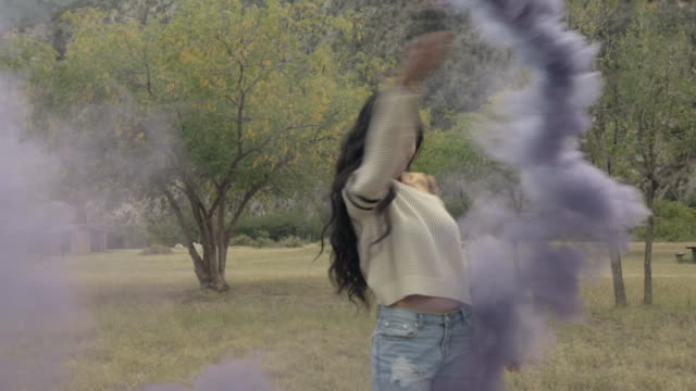 Young woman with smoke grenade