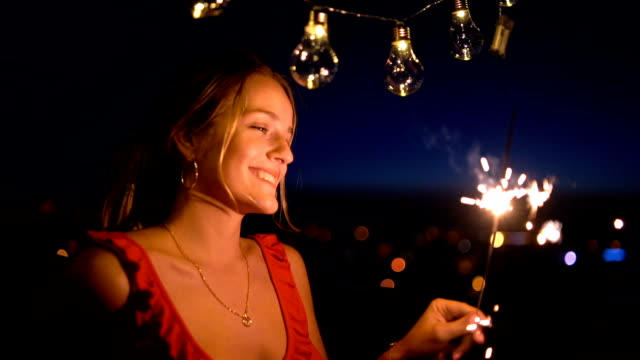 young woman with sparkler on rooftop - balcony stock videos & royalty-free footage