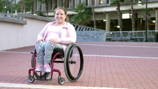 vídeos de stock, filmes e b-roll de mulher nova com espinha bífida, sentando-se na cadeira de rodas - cadeira de rodas equipamento ortopédico