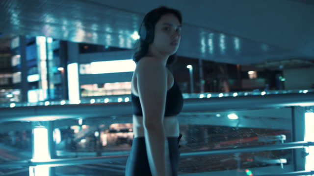 young woman with sports bra walking at night in tokyo, japan - leggings stock videos & royalty-free footage