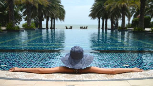 Jonge vrouw met stro hoed op het zwembad