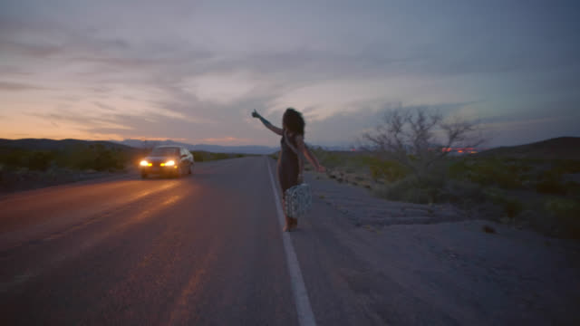 vídeos y material grabado en eventos de stock de young woman with suitcase hitchhikes along desert highway sticking thumb out as car passes and walking the white line. - perdido