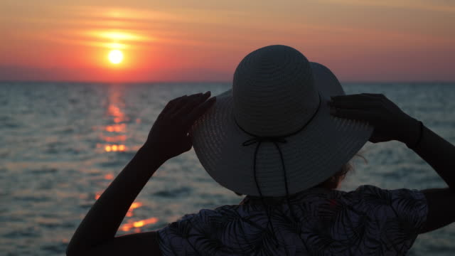 young woman with sun hat near the ocean during beautiful sunset. relaxation at beach on summer vacation - sun hat stock videos & royalty-free footage
