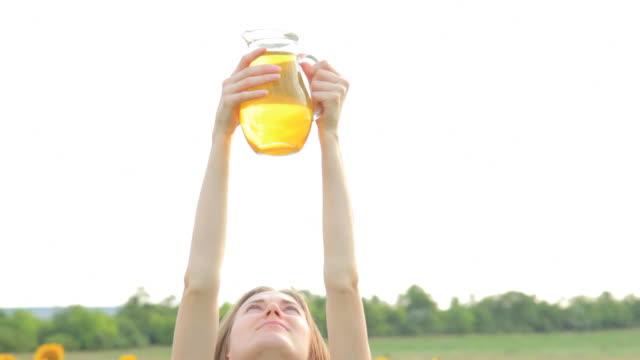 vidéos et rushes de jeune femme hd avec pichet huile de tournesol - huile de table