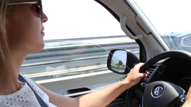vídeos de stock e filmes b-roll de a young woman with sunglasses and a white dress a tourist from germany drives a van through tunnels in italy at the coast at the ligurian sea the... - banco do passageiro